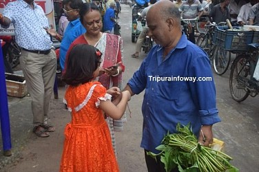 A little girl tying Rakhi to mark Raksha Bandhan to citizens in Agartala. TIWN Pic Aug 15