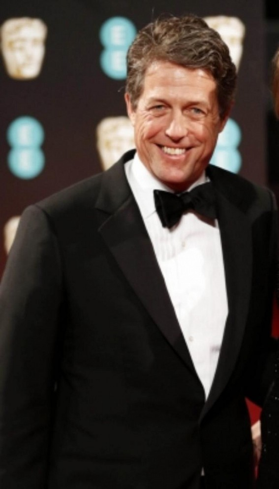 Hugh Grant 'trying to be a young father in an old man's body' at 60